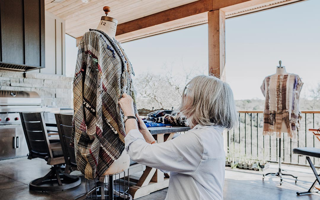 Kathy Utts draping a piece of clothing made with SAORI fabric on the back porch of the new Wimberley Valley SAORI studio